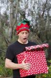 Homme étonné tenant des cadeaux de Noël Photographie stock libre de droits