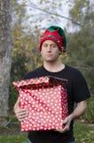 Homme étonné tenant un cadeau de Noël Photographie stock libre de droits