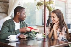 Homme étonnant son amie avec le cadeau Images stock