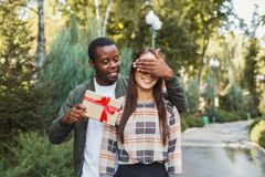 Homme étonnant son amie avec le cadeau Image libre de droits
