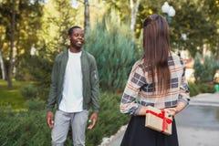 Homme étonnant son amie avec le cadeau Photos stock