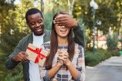 Homme étonnant son amie avec le cadeau Photo libre de droits