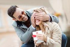 Homme étonnant son amie avec un cadeau Photos libres de droits