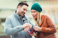 Homme étonnant son amie avec un cadeau Images stock