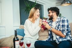 Homme étonnant son amie avec un cadeau Image stock