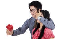 Homme étonnant une femme avec un cadeau Image libre de droits