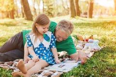 Homme étreignant sa petite magazine de lecture de petite-fille Photographie stock