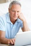 Homme aîné à l'aide de l'ordinateur portable Photos libres de droits