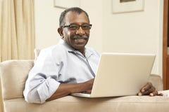 Homme aîné à l'aide de l'ordinateur portatif à la maison Image libre de droits