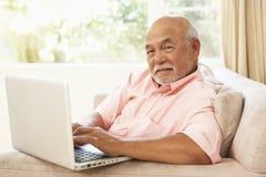 Homme aîné à l'aide de l'ordinateur portatif à la maison Photographie stock libre de droits