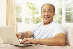 Homme aîné à l'aide de l'ordinateur portatif à la maison Photographie stock