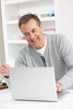 Homme aîné à l'aide de l'ordinateur portatif à la maison Photos libres de droits