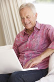 Homme aîné à l'aide de l'ordinateur portatif à la maison Images stock