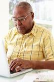 Homme aîné à l'aide de l'ordinateur portatif à la maison Photo stock