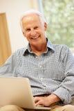 Homme aîné à l'aide de l'ordinateur portatif à la maison Photos stock