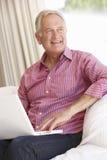 Homme aîné à l'aide de l'ordinateur portatif à la maison Images libres de droits