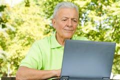Homme aîné à l'aide de l'ordinateur portatif Photos libres de droits