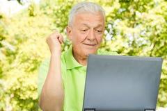 Homme aîné à l'aide de l'ordinateur portatif Image libre de droits