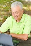 Homme aîné à l'aide de l'ordinateur portatif Photographie stock