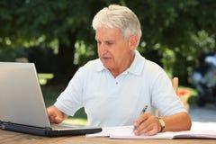 Homme aîné à l'aide de l'ordinateur portatif dans le jardin Photographie stock
