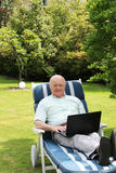 Homme aîné à l'aide de l'ordinateur portatif dans le jardin Image libre de droits
