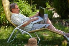 Homme aîné à l'aide de l'ordinateur portatif extérieur Images libres de droits