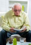 Homme aîné affichant un livre Photographie stock libre de droits