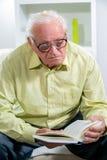 Homme aîné affichant un livre Photos libres de droits
