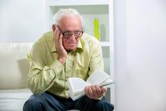 Homme aîné affichant un livre Image libre de droits