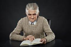 Homme aîné affichant un livre Photo libre de droits
