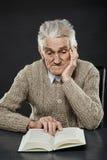 Homme aîné affichant un livre Images stock