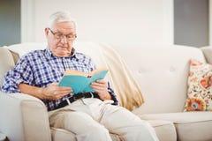 Homme aîné affichant un livre Photographie stock