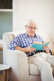 Homme aîné affichant un livre Image stock