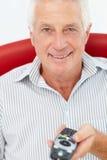 Homme aîné avec à télécommande Images libres de droits
