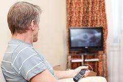 Homme aîné avec à télécommande et le téléviseur Photographie stock libre de droits