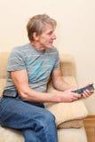 Homme aîné avec à télécommande et le téléviseur Image libre de droits