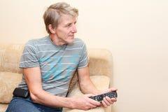 Homme aîné avec à télécommande et le téléviseur Photo stock