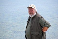 Homme aîné avec de l'eau à l'arrière-plan Photographie stock libre de droits