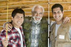 Homme aîné avec deux fils retenant les cannes à pêche Photographie stock libre de droits