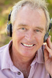 Homme aîné avec l'écouteur Images stock