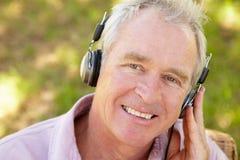 Homme aîné avec l'écouteur Image libre de droits