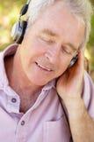 Homme aîné avec l'écouteur Photos stock
