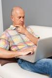 Homme aîné avec l'ordinateur portatif à la maison Photos libres de droits