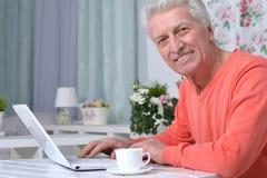 Homme aîné avec l'ordinateur portatif Images libres de droits