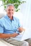 Homme aîné avec l'ordinateur portatif Image stock