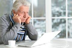 Homme aîné avec l'ordinateur portatif Images stock