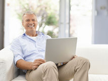 Homme aîné avec l'ordinateur portatif Photographie stock libre de droits