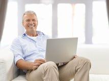 Homme aîné avec l'ordinateur portatif Photos stock