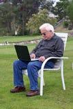 Homme aîné avec l'ordinateur portatif au golf Photo libre de droits