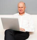 Homme aîné avec l'ordinateur portatif en ligne Images libres de droits